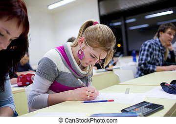 pretty female college student sitting an exam in a classroom