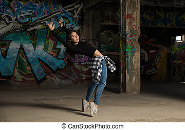 Pretty female dancer in abandoned building