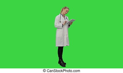 Pretty female doctor with stethoscope glad to get a good results using digital tablet on a Green Screen, Chroma Key.