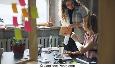 Pretty female entrepreneur sharing ideas to her colleague while working on design project in modern office. She is showing her information on page, they are talking and watching screen together.