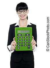 Pretty female executive showing calculator