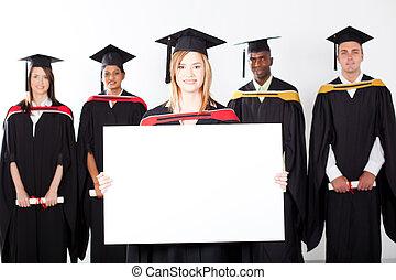 pretty female graduate holding white board