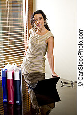 Pretty female Hispanic office worker in boardroom