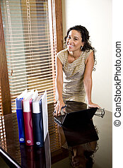 Pretty female Hispanic office worker in boardroom