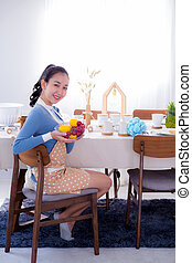 Pretty female holding bowl with a smile in kitchen