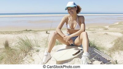 Pretty female looking at camera on surfboard - Smiling young...