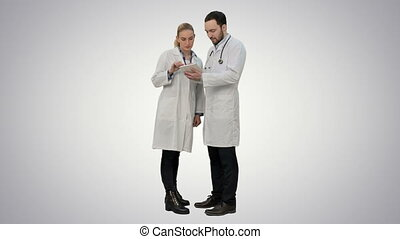 Pretty female nurse and handsome doctor with stethoscope using digital tablet on white background.