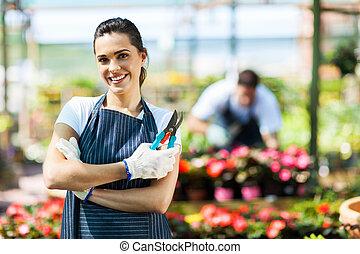 pretty female nursery worker portrait with pruner