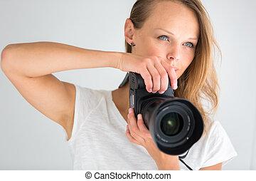 Pretty, female photographer with digital camera