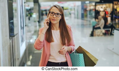 Pretty female student is talking to friends on mobile phone...