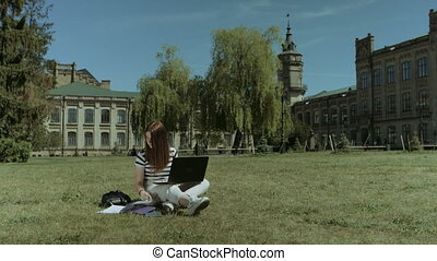 Pretty female student working on laptop on lawn