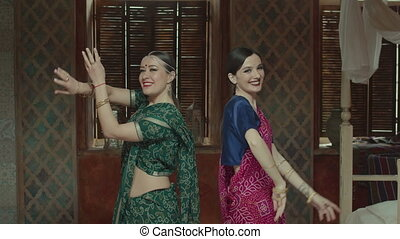 Pretty females in sari dancing in indian manner - Widely...