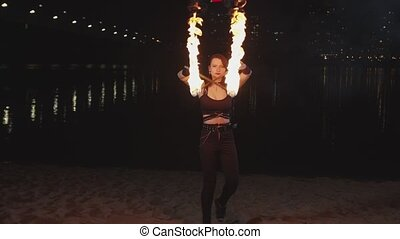 Pretty firegirl juggling lit torches sitting down - Skillful...