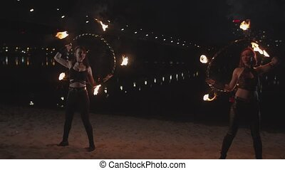 Pretty firegirls working with fire hoops outdoor - Stylish...