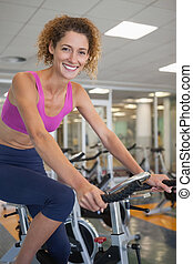 Pretty fit woman on the spin bike smiling at camera at the...