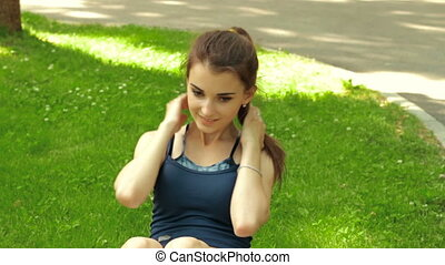 pretty fitness girl lying on the grass and shakes press