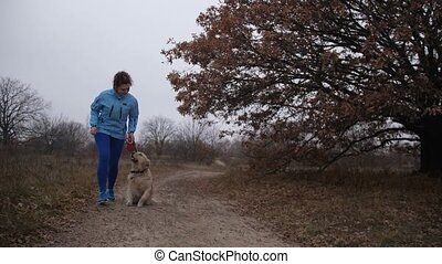 Pretty fitness woman and dog jooging in fresh air - Positive...