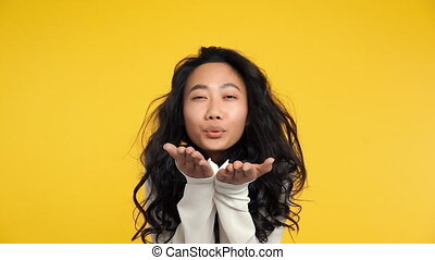 Pretty flirting woman sending kiss to you on yellow...