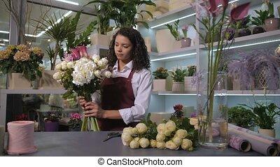 Pretty florist arranging flowers for bouquet - Attractive...