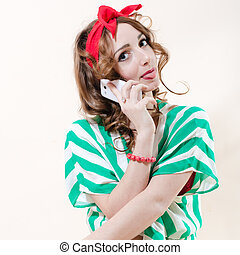 pretty funny pinup woman speaking on mobile cell phone showing tongue studio shot over white background