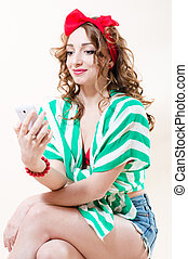 Pretty funny pinup woman speaking on mobile studio shot over white background
