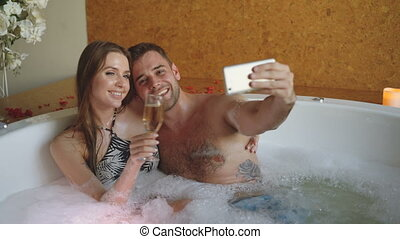 Pretty girl and her loving boyfriend are taking selfie with champagne glasses using smartphone while bathing in bathtub. They are smiling and posing looking at camera.