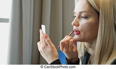 Pretty girl applying red lipstick while sitting in cafe,...