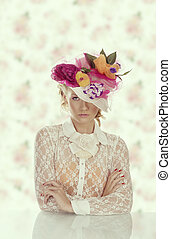 pretty girl behind table with vintage shirt and flowers on the hat, she is in front of the camera and looks in to the lens