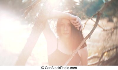 pretty girl brunette portrait large lips wind develops hair portrait in in the forest sunset silhouette in a red dress. slow motion video. brunette woman girl hair hairstyle lips strong wind on the nature. girl lips wind hair concept lifestyle