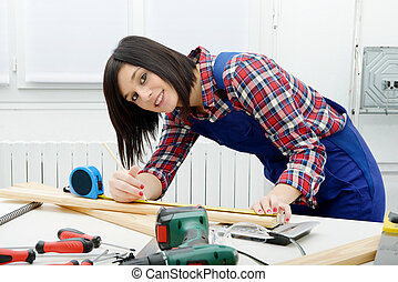 pretty girl builder measuring a plank of wood