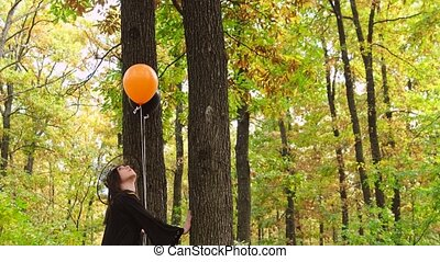 Pretty girl came close to trees looking up, wearing Halloween clothes with the hat and holding two color balloons in her hand. High quality 4k footage
