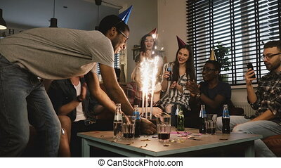 Pretty girl celebrates birthday with her friends. Multi ethnic party with cake and Bengal light sparkling firework. 4K.