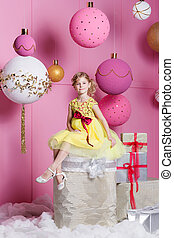 Pretty girl child 6 years old in a yellow dress. Baby in Rose quartz room decorated holiday.