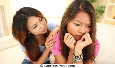Pretty girl comforting sister on couch in bright living room