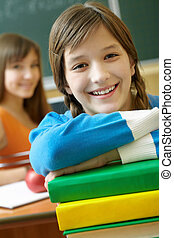 Pretty girl - Confident student looking at camera with stack...