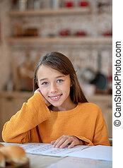 Cute girl in orange shirt feeling positive