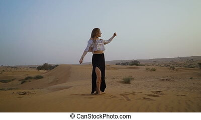 Pretty girl dances in the desert. Beautiful woman is dancing at sunset. Slow motion