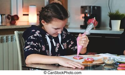 Pretty girl decorating cookies with color sugar glaze in the evening at home, happy to spent time together with her family.