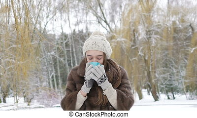 Pretty girl drinking a cup of hot beverage outdoor in winter day