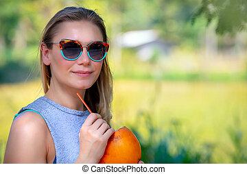 Pretty girl drinking coconut water - Portrait of a pretty ...