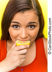 pretty girl eating fresh lemon. beautiful girl isolated on...