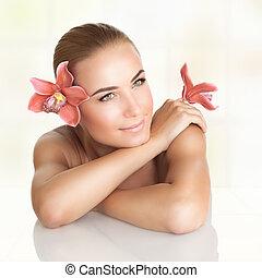 Pretty girl enjoying dayspa - Pretty girl with orchid...
