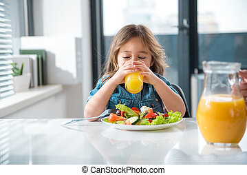 Pretty girl enjoying healthy orange drink in kitchen