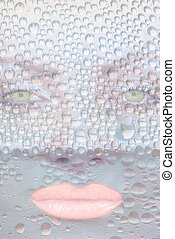 Pretty girl face with green eyes against transparent water drops as background.