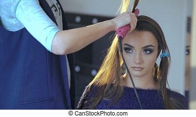 Pretty girl getting her hair dressed in hair salon