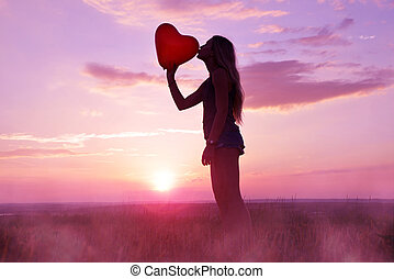Pretty girl giving a kiss red balloon in the shape heart.