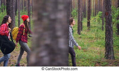 Pretty girl guitarist is hiking with friends and carrying guitar gig bag walking in forest with multiethnic group of young people. Nature, youth and music concept.