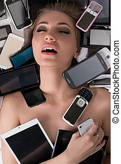 Pretty girl has orgasm from excess of gadgets. Photo concept