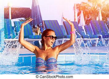 Pretty girl having fun in the pool