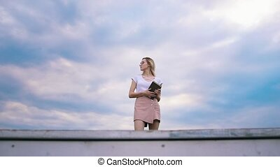 Pretty girl hipster with a book against the blue sky sits...
